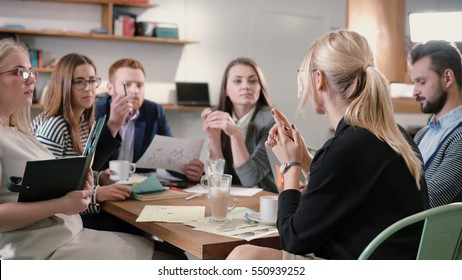 Creative business team at table in a modern startup office. female speaker offers a great idea and the team supports her