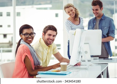 Creative business team working hard together on pc in casual office