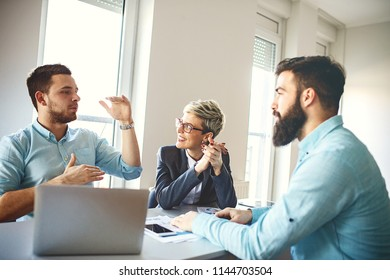 Creative business team working on project. Creative director is showing chart to the workers.