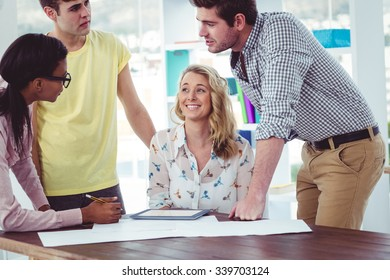 Creative business team working on a tablet together in casual office