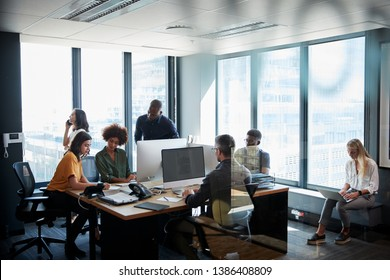 Creative business team working together in a busy casual office, seen through glass door