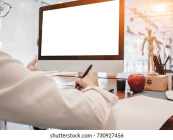 Creative businessman drawing on graphic tablet while using modern desktop computer in office. Blank screen for graphic display montage.