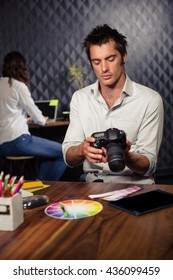 Creative businessman looking at picture on camera in office
