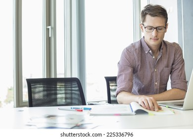 Creative businessman reading file at desk in office