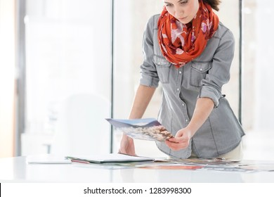 Creative businesswoman reviewing photographs at desk