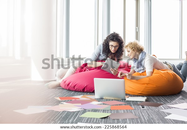 Creative businesswomen using tablet PC while relaxing on beanbag chairs at office