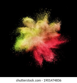 Creative chaotic powder explosion or splash in yellow and red colors on a black background with copy space.