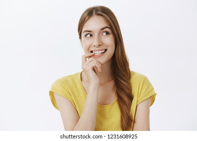 Creative charismatic cute happy woman with braid in yellow t-shirt biting finger from curiosity looking right intrigued and interested posing enthusiastic and joyful over gray wall, having idea