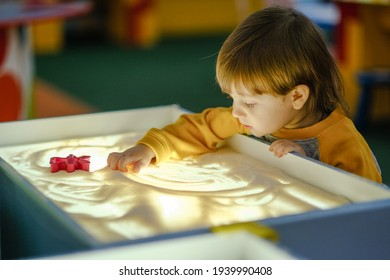 Creative child development. Baby draws sand on glass. Early development of children. Development of shallow motility and tactile sensations.