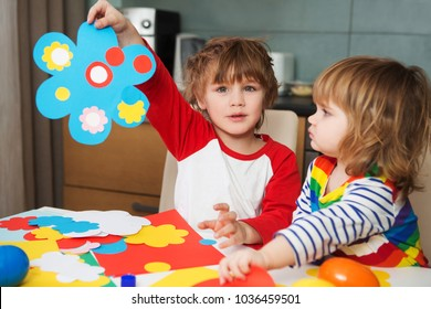 Creative children play with craft. ?ute preschool children prepare together Paper decor. Tools and materials for children's art creativity on table.  Easter decor.
