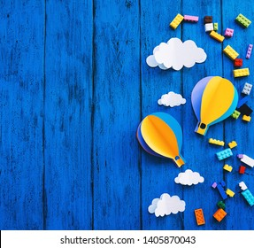 Creative children's background with copy space for text, top view. Paper crafts, colourful toy bricks on blue wood table. DIY, study languages, kids creativity class, adventure or travel themes