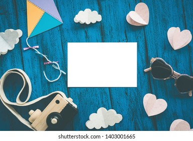 Creative children's background, top view. Paper crafts, photo camera with blank card for text on blue table. DIY, study languages, kids creativity class or travel concept. In vintage color tone