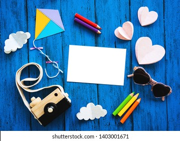 Creative children's background, top view. Paper crafts, colored pencils, photo camera with blank card for text on blue table. DIY, study languages, kids creativity class or travel concept
