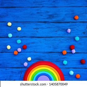 Creative children's waldorf or montessori school concept. Wood rainbow and multicolored craft materials on blue table. Kids art class, kindergarten, preschool background