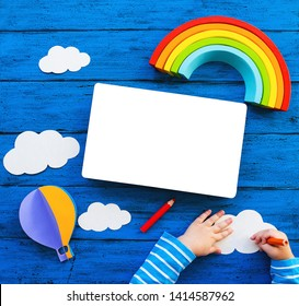 Creative children's waldorf or montessori school concept. Paper crafts, colored pencils, wood rainbow and blank book with child hands on blue table. Kids art class, kindergarten, preschool background