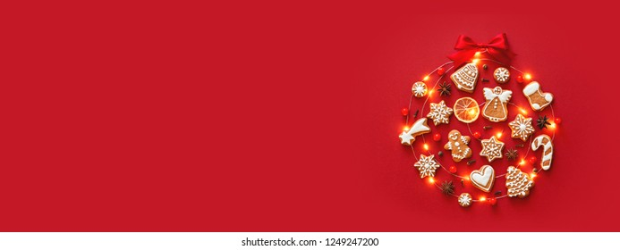 Creative Christmas ball made of iced gingerbread cookies, anise stars, berries, orange chips, decorated red ribbon bow on red background. New Year banner. Top view.