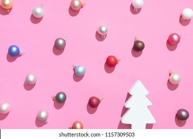 Creative Christmas baubles decoration pattern with christmas tree and pink background. Minimal flat lay concept.