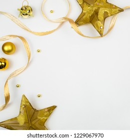 Creative Christmas layout. Golden stars, ribbons and ball on white background whit copy space. Border arrangement. Flat lay top view.