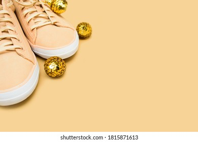 Creative Christmas shoe shop background with beige sneakers and gold decoration