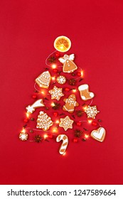 Creative Christmas tree made of iced gingerbread cookies, anise stars, berries, orange chips, decorated red ribbon bow on red background. New Year greeting card concept. Top view.