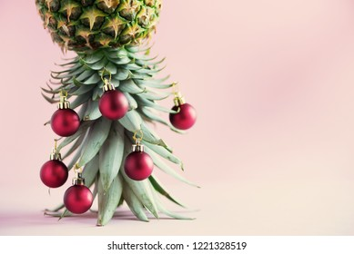 Creative Christmas tree made of pineapple and red bauble on pink background, copy space. Greeting card, decoration for new year party. Holiday concept
