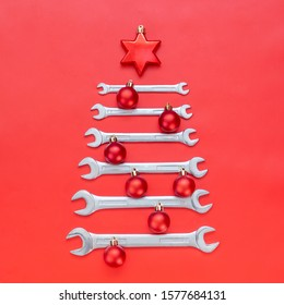 Creative christmas tree on red background, made of wrenches. Industrial greeting card and happy new year concept. Square