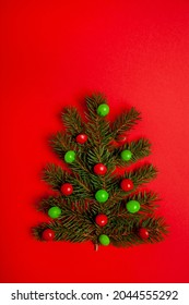 Creative Christmas tree out of small branches and red and green skittles candies, lay flat on bright red background  - Shutterstock ID 2044555292