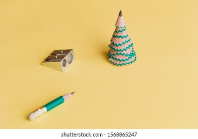 Creative christmas tree. Pencil for shavings, pencil and sharpener on a yellow background. Christmas concept in office. Selective focus. Close up.