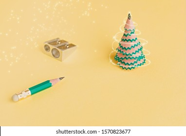 Creative christmas tree. Pencil, shavings and sharpener on a yellow background. Christmas concept in office. Selective focus. Close up.