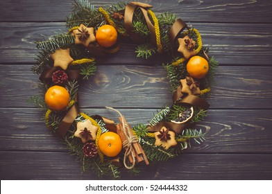 Creative Christmas wreath. An unusual idea for a holiday home decor. Natural interior decor on wooden background.