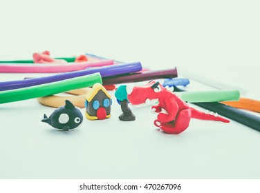 Creative clay animal model. Red dinosaur, whale, house and tree from children bright play dough. Studio shoot. Vintage tone effect.