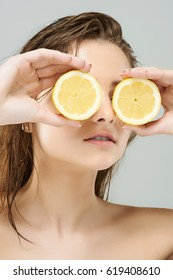 Creative close up portrait of a beautiful young women holding juicy lemon slices in front of eyes