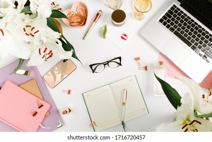 Creative colorful female workspace with laptop computer, glasses, cosmetics, flowers, colorful notebooks, golden clips on white desk. Flat lay, top view