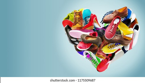 Creative colorful heart-shaped arrangement of an assortment of ladies high-heeled stiletto shoes, sneakers, trainers, boots and leather footwear for men in rainbow colors on blue with copy space