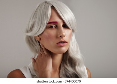 creative coloured hair of model. grey hair pink brows
