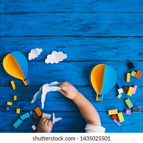 Creative colourful kid's background, top view. Paper crafts, toy bricks, playing or making child hands on blue wood table.