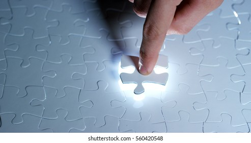 A creative completes the white puzzle putting the last missing piece. Concept: cooperation, teamwork, creativity, and access solution.