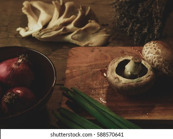 Creative composition with different kind of mushrooms, red onions, leeks, lavender and  kitchen tools on a wooden table