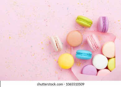 Creative composition with envelope and cake macaron or macaroon on pink pastel background top view. Flat lay.
