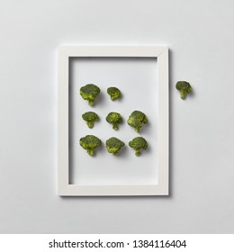 Creative composition with freshly picked green broccoli in a frame and one part out of it on a light gray background, place for text. Flat lay. Vegan concept.