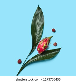 Creative composition of fruits of Pitahaya, lychees and green leaves in the form of a flower on a blue background copy space share text. Flat lay