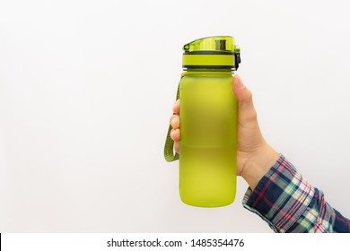 Creative composition with woman's hand holding bright green plastic free reusable bottle  on white background with copy space. Ecology protection concept. BPA free materials. Zero waste concept.