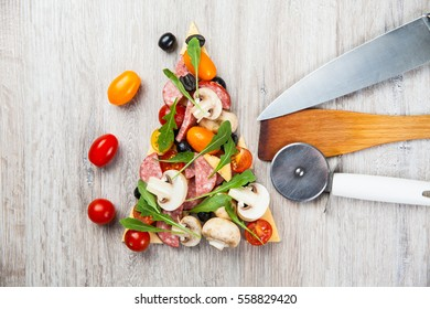 Creative composition of ingredients tomatoes, cheese, salami, mushrooms, arugula, olives in the form of a slice of pizza with knife and spatula, pizza cutter.