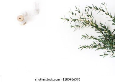 Creative composition made of green Eucalyptus parvifolia branches, silk ribbon and wooden spool on white table background. Feminine wedding styled stock flat lay image, top view. Empty negative space.