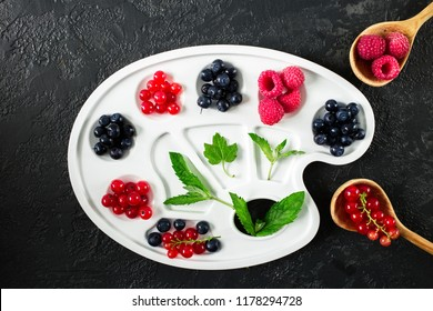 Creative composition  on palette  with different fresh berries. Raspberries, blueberries, red currants. Summer harvest. Healthy eating concept. Collage