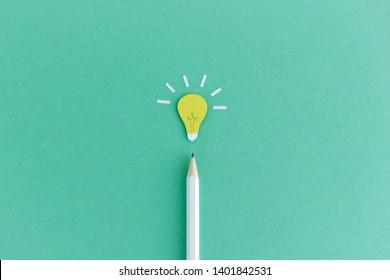 Kreative Zusammensetzung des Bleistiftes mit kleiner Papierleuchte, die oben auf grünem Hintergrund leuchtet