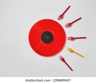 Creative composition with red vinyl record and plastic colored forks on a gray background. Concept of fertilized egg by sperms.
