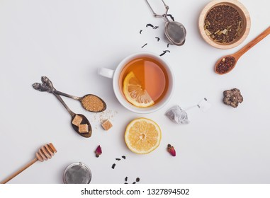 Creative composition witn variety of tea, sugar, lemon and other accessories for tea preparation, top view