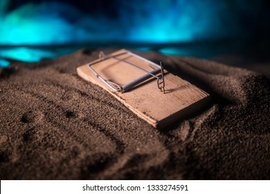 Creative concept. Artwork decoration of mousetrap in sand on dark toned foggy background. Mousetrap captured a man. Selective focus