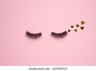 Creative concept beauty fashion photo of lashes extensions brush on pink blue background.